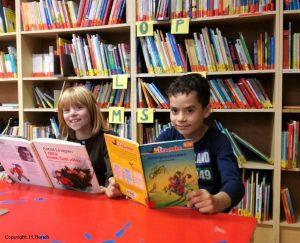 Zwei Kinder mit einem Buch in der Hand in einer Bibliothek