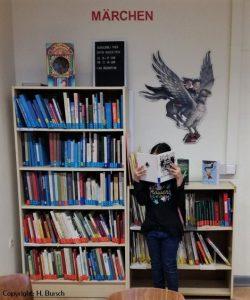 Ein Kind steht vor einem Bücherregal